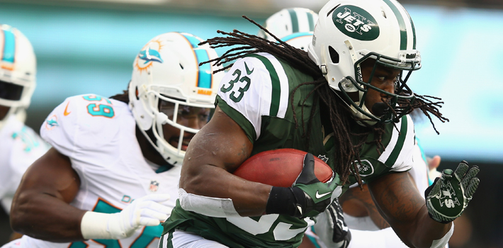 EAST RUTHERFORD, NJ - DECEMBER 01:   Chris Ivory #33 of the New York Jets runs with the ball as  Koa Misi #55 of the Miami Dolphins trails during their game at MetLife Stadium on December 1, 2013 in East Rutherford, New Jersey.  (Photo by Al Bello/Getty Images)